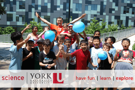 Group of volunteers and children participants holding balloons and smiling at camera.