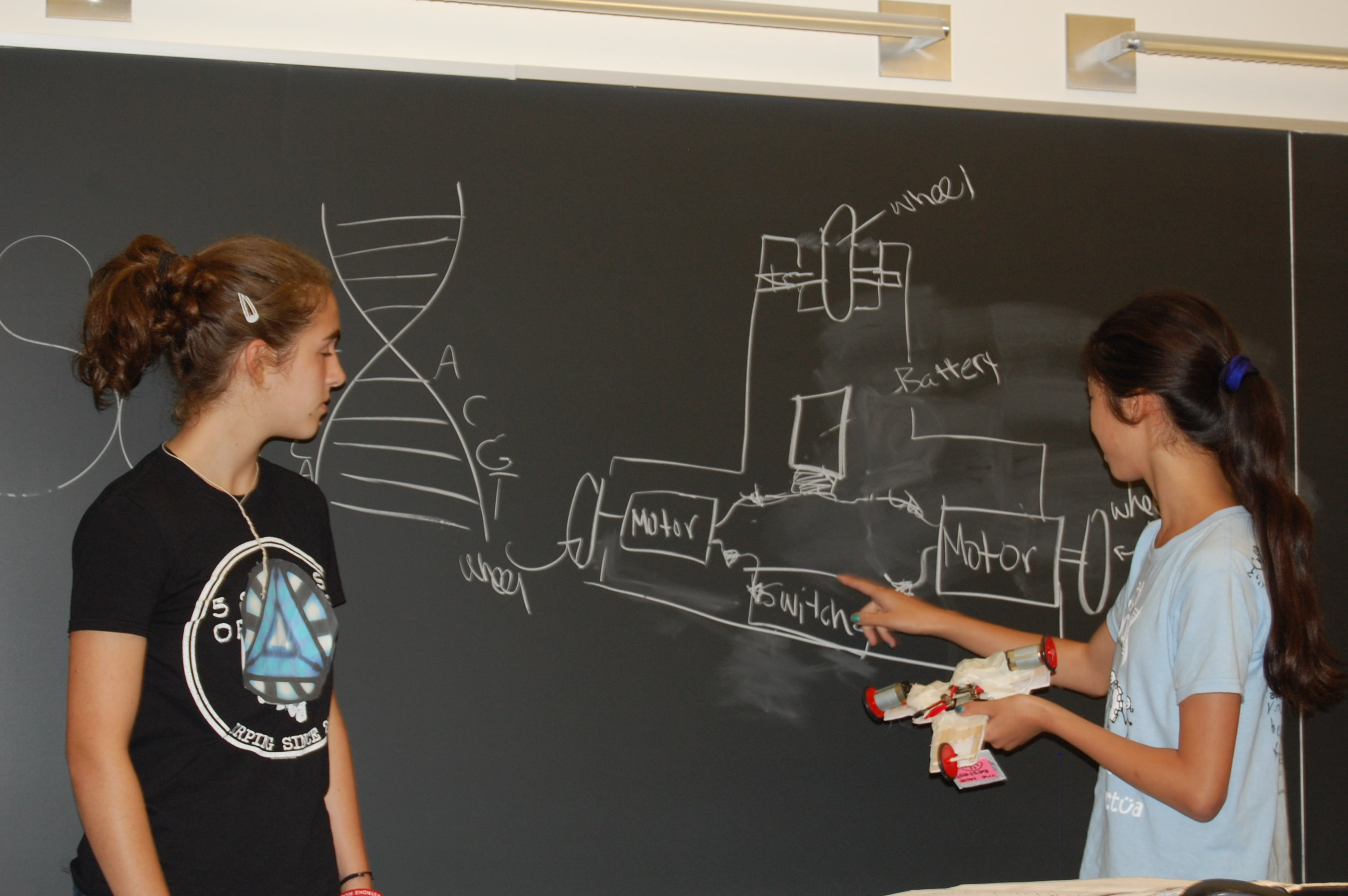 Two young females in front of chalkboard with technical writing on it.