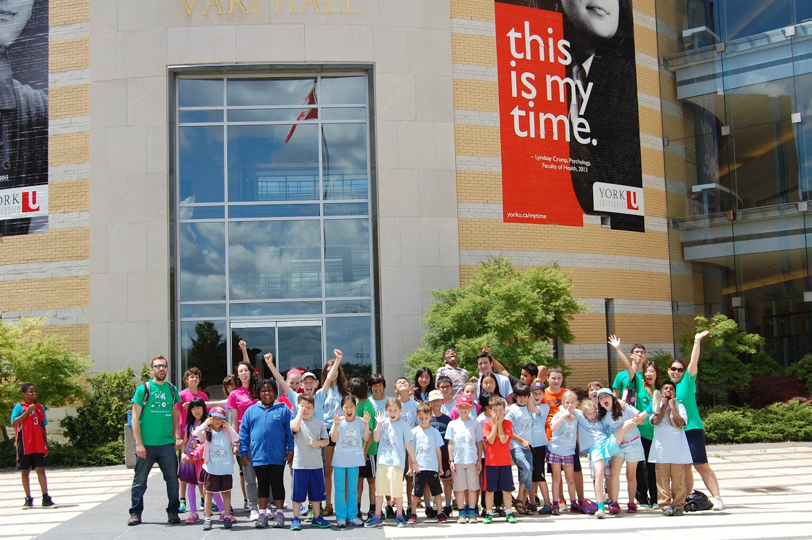 Happy group of volunteers and participants posed in front of York campus building.