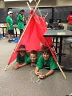 Young kids under makeshift tent in classroom.