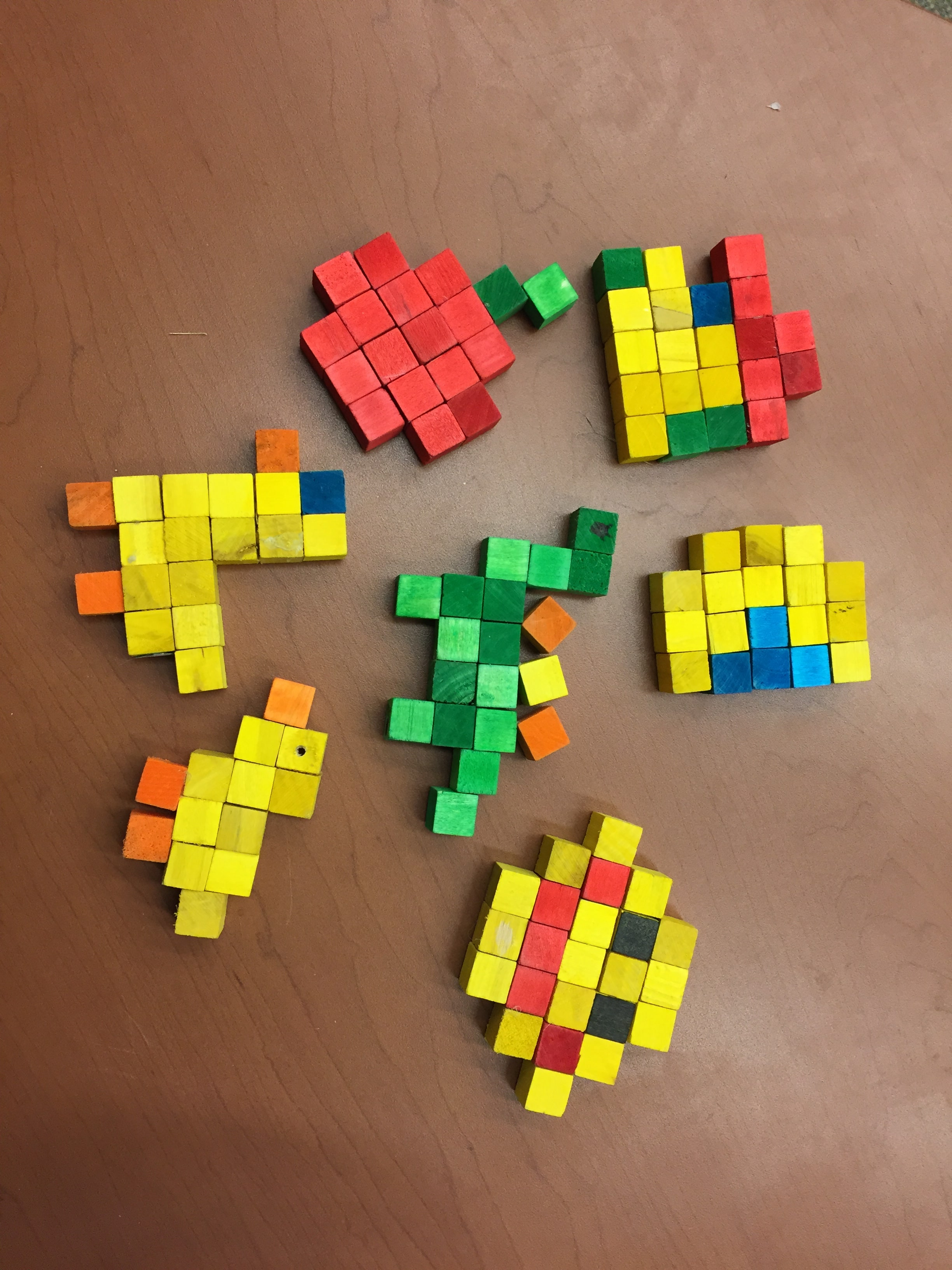 Colourful small blocks arranged to form animal shapes on table.