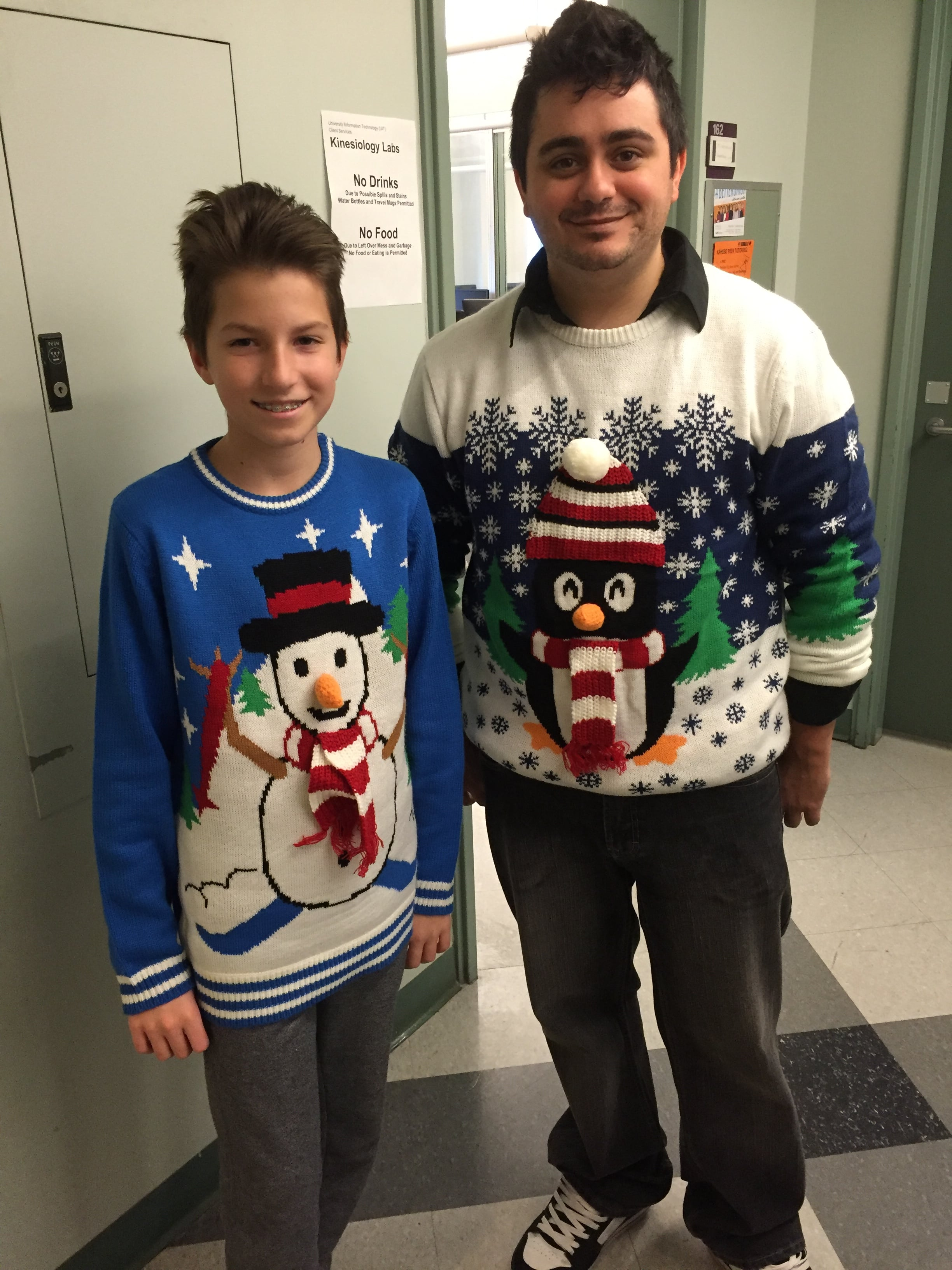Volunteer and student wearing Christmas themed sweaters.