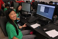 Young girls smiling for camera while in computer classroom.